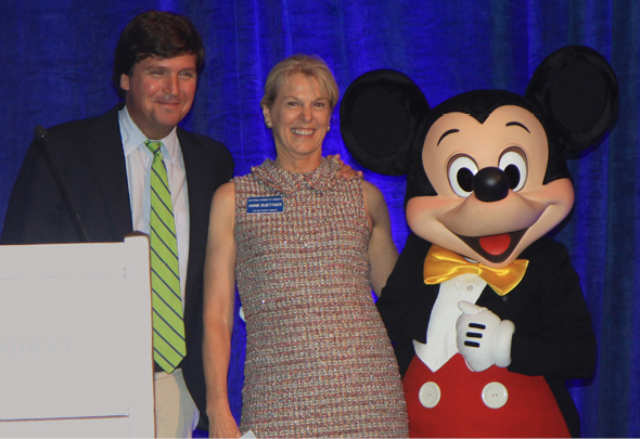 """Fox News journalist and commentator Tucker Carlson (left) shares the stage following his introduction at the CalChamber Board of Directors recent dinner by Anne Buettner, CalChamber Board chair, a senior vice president of The Walt Disney Company, assisted by Mickey Mouse. Assessing the national political scene, Carlson predicts a """"zany primary season."""""""